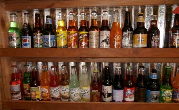 A shelf full of oddly flavored soda pops