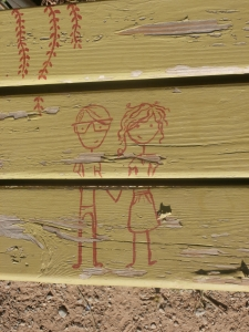 Red stick-figure couple painted on green bench