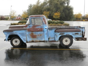 An old, rusty pick-up truck in a Walmart parking lot