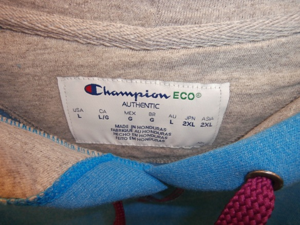 A photo of a tag on a hoodie listing sizes around the world