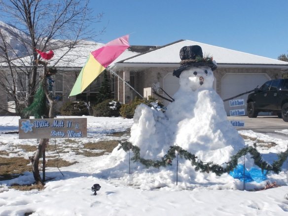 A snowman standing under an umbrella