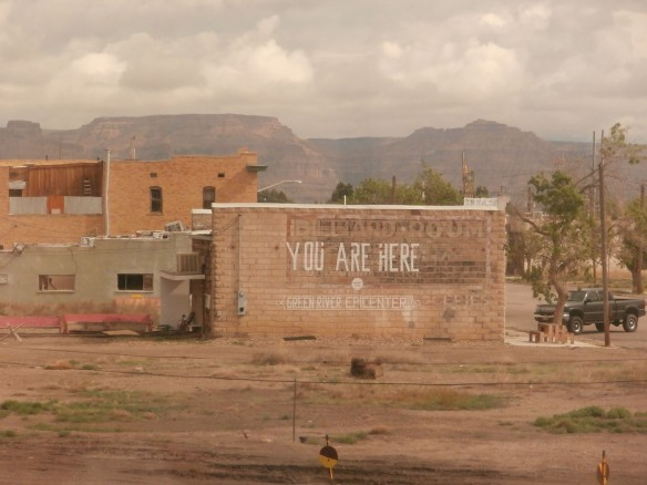 "A sign painted on the side of a brick building, ""You Are Here, Green River Epicenter"""