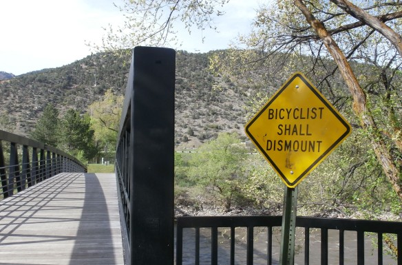 "A sign next to a bike path bridge, ""Bicyclist shall dismount"""