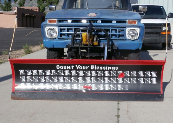 A plow mounted on a pickup truck. The words