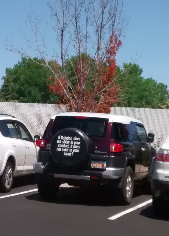 "A tire cover on a vehicle carries a message: ""If Religion does not show in your conduct, it does not exist in your heart!"""