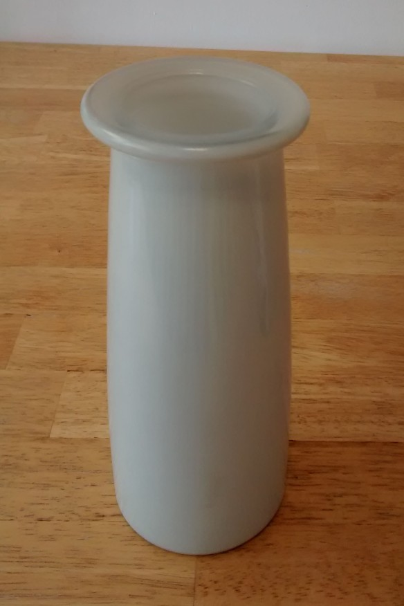 A white vase with an area of flaked-off finish