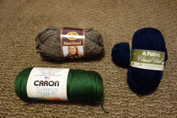 A photo of Caron Simply Soft yarn, Lion Brand Heartland yarn, and Patons Classic Wool DK Superwash yarn