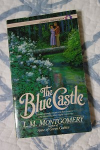 A paperback novel titled The Blue Castle by L. M. Montgomery