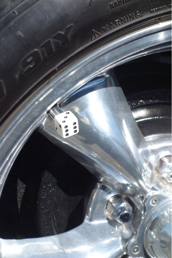 A decorative tire valve cap shaped like a die