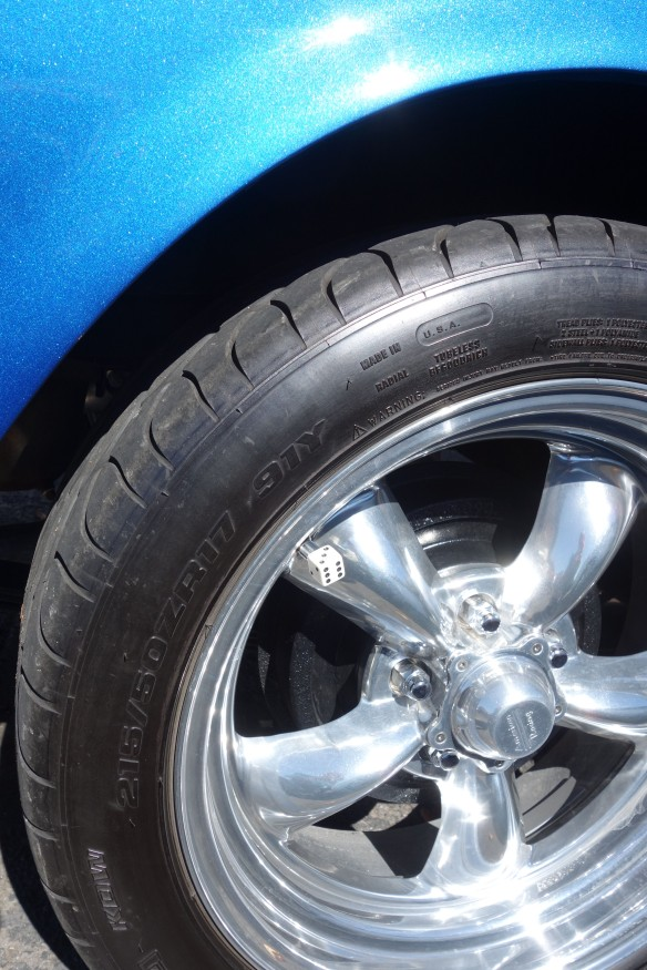 A decorative tire valve cap shaped like a die