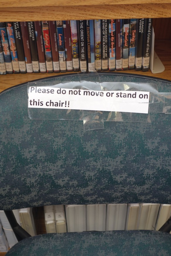 "Sign taped to a chair: ""Please do no move or stand on this chair!!"""