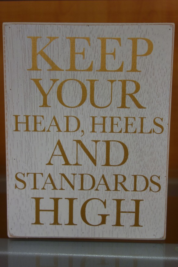 "A decorative sign: ""Keep your head, heels, and standards high"""