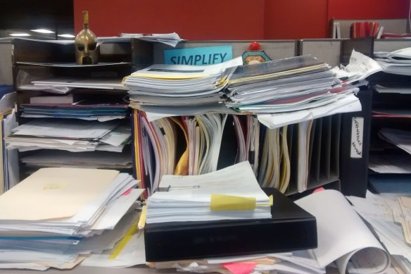 "A sign reading ""Simplify"" is almost covered by a stack of paperwork"