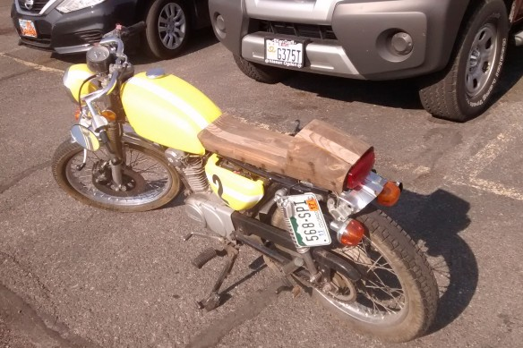 A motorbike with a wooden saddle