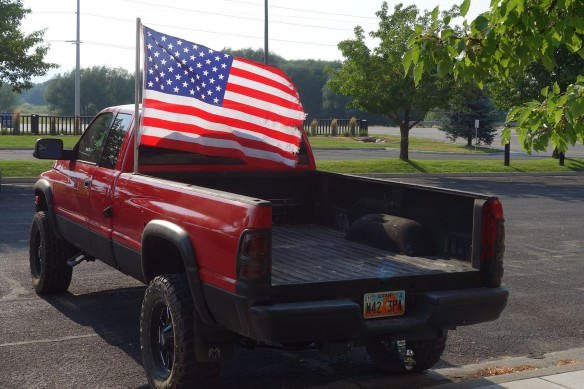 A red pickup truck flying a large American flag