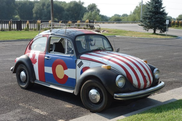 A VW bug painted with a variety of international flags