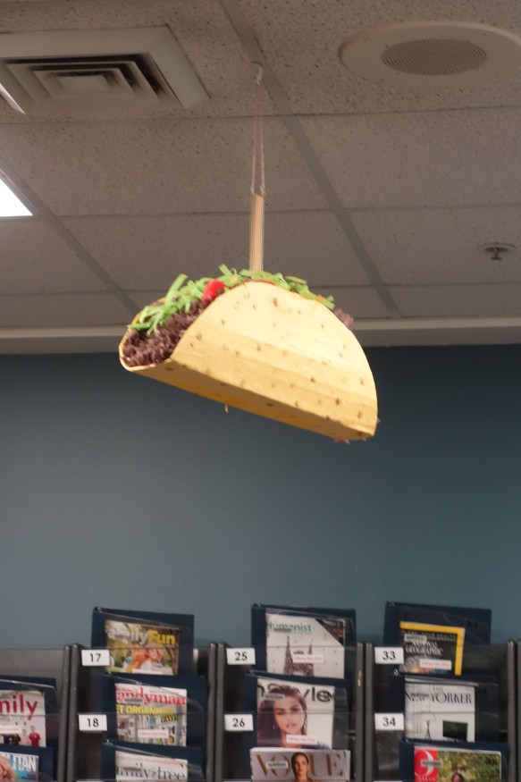 A mobile shaped like a hard-shelled taco hanging from a library ceiling