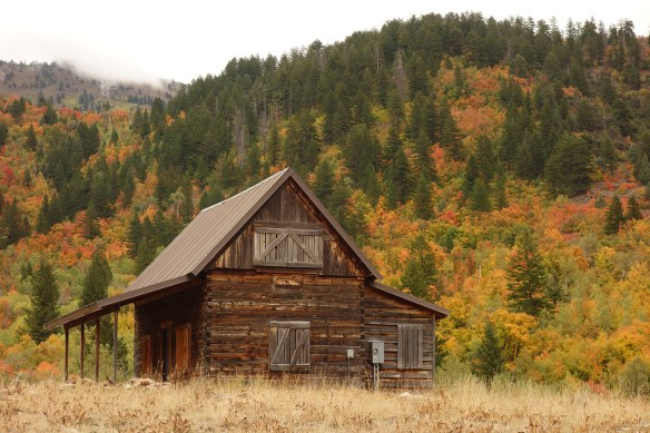A log cabin against a backdrop of red and yellow fall color