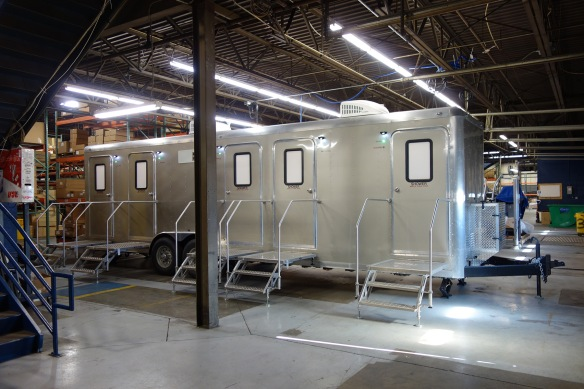 A large shower trailer parked inside a warehouse