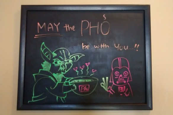 "A sign in a Vietnamese pho restaurant reading: ""May the phos be with you!'"""