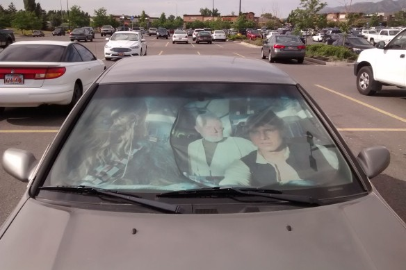 A car sun shade showing Star Wars characters Chewbacca, Obi-wan Kenobi, and Han Solo