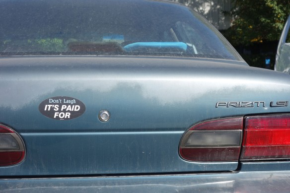 "A car bumper sticker stating ""Don't laugh, it's paid for"""