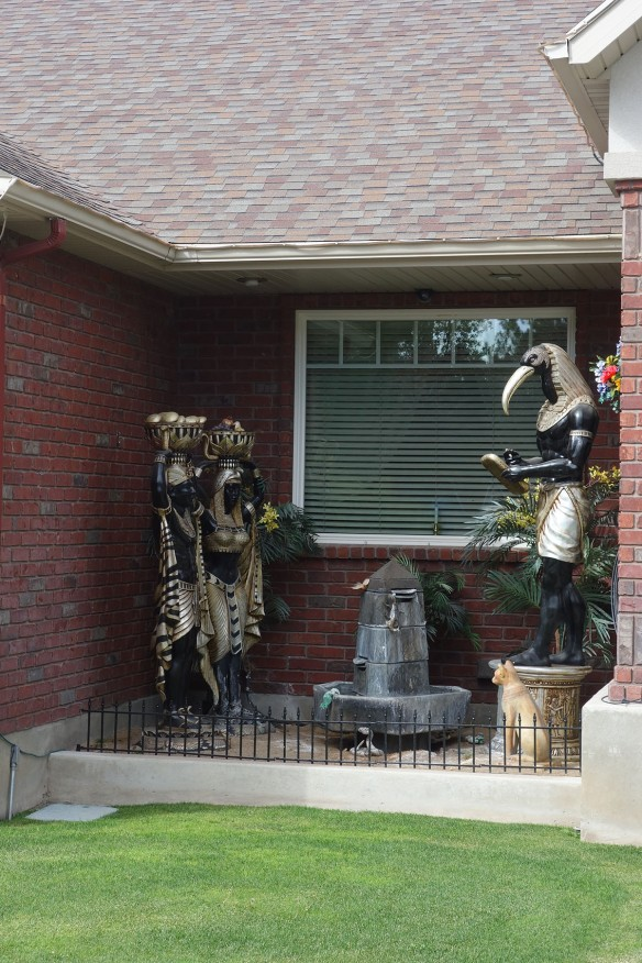 Larger-than-life statues of Egyptian gods outside a suburban ranch home