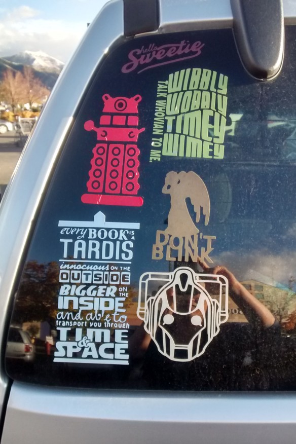An assortment of Doctor Who stickers on the rear windshield of a vehicle