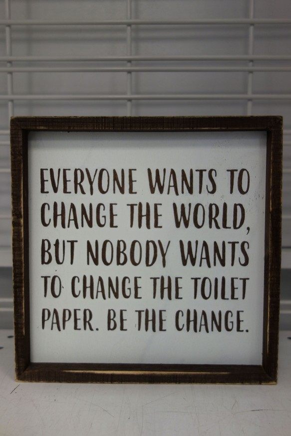 "A decorative sign that reads, ""Everyone wants to change the world but nobody wants to change the toilet paper. Be the change."